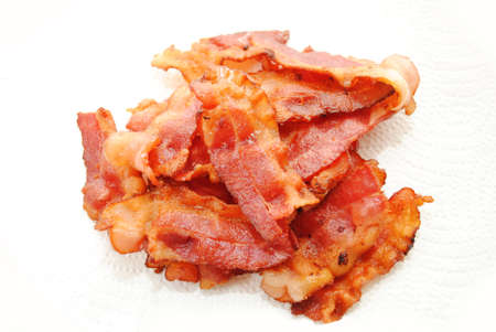 high calorie foods: Crispy Fried Bacon Drying on Paper Towel Stock Photo