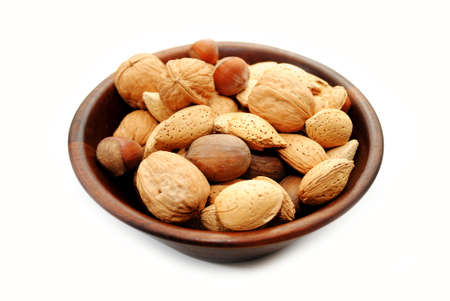 over white: Mixed Whole Nuts in a Wooden Bowl Over White