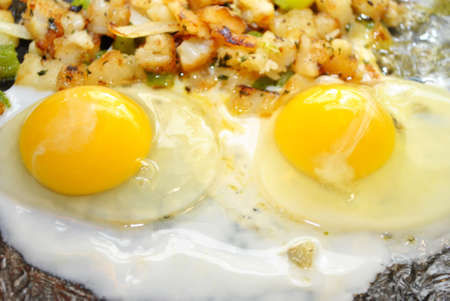 browned: Two Over Easy Eggs Cooking in a Pan Stock Photo