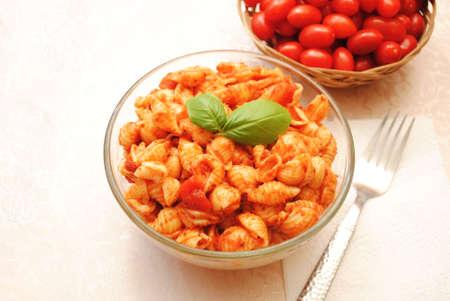 Un bol de pâtes de coquille végétarienne avec des tomates cerises entières en arrière-plan Banque d'images - 58635411