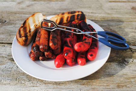 grill tongs sausage: Grilled Hotdogs with Toasted Buns Ready to Serve at a Cookout Stock Photo