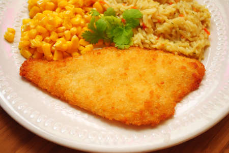 Gepaneerde gebakken vis geserveerd met Corn & Rice Stockfoto