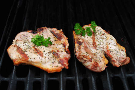 garnished: Two Perfectly Cooked Pork Chop on a Grill Garnished with Fresh Parsley Stock Photo