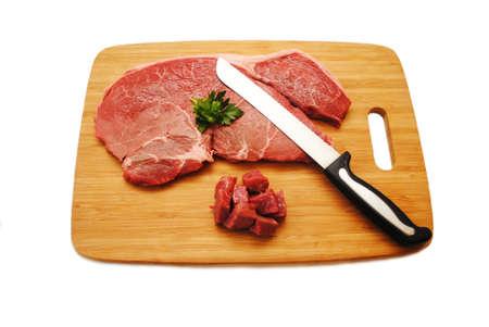 Cutting a Raw Steak on a Wooden Cutting Board