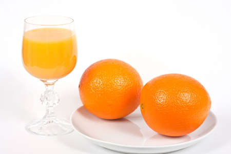 Two Oranges on a White Plate with a Glass of Orange Juice Stock Photo