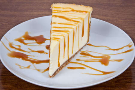 Cheesecake With Caramel Drizzled on Top Served on a White Plate Imagens