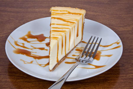 Cheesecake With Caramel Drizzled on Top Served on a White Plate With a Fork Stock Photo - 6594765