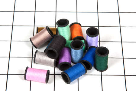 Colorful Spools Of Thread On A Sewing Mat
