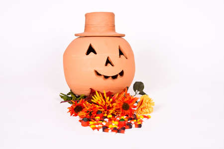 Halloween Jack-O-Lantern with flowers and candy on a white background.