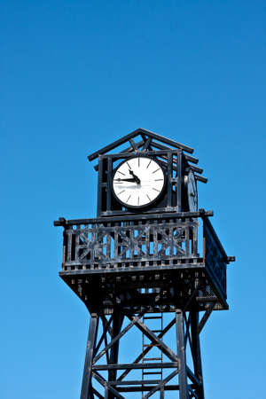 ironworks: Clock on top of a tower with a ladder and blue sky in the background.