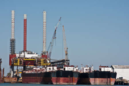 Large ships docked at an oil rig under construction with multiple cranes working. Stock Photo