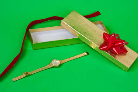 Christmas watch with box, ribbon and bow on green background Stock Photo