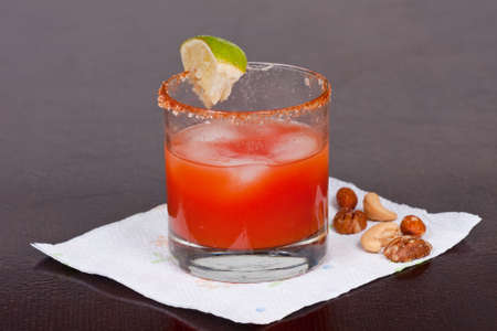 Bloody Mary Cocktail with salt  lime and nuts photo
