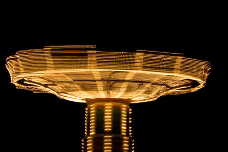 Carnival ride spinning in the sky lit up at night