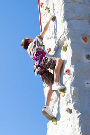 Young boy determination while climbing up an artificial rock wall photo