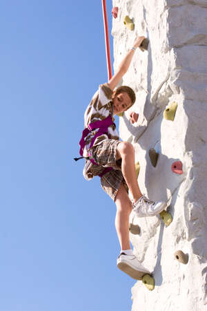 Happy Young boy climbing up an artificial rock wall Stock Photo
