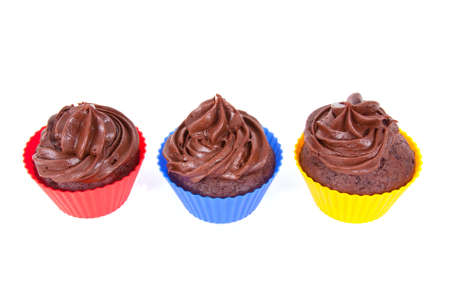 Three chocolate cupcakes in red, blue and yellow holders Stock Photo
