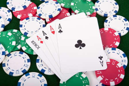 Winning Four aces and a joker poker hand with poker chips Stock Photo - 11027145