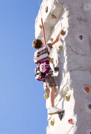 Young boy climbing up an artificial rock wall