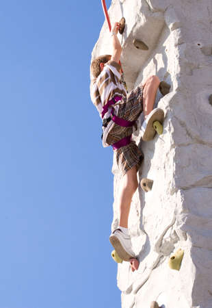 Young boy climbing up an artificial rock wall