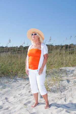 Woman barefoot in the sand dressed in fashion