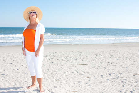 Woman at the beach wearing orange and white with hat and sunglasses Stock Photo