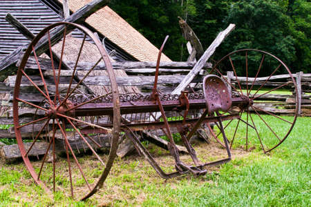 Old antique farm machine rusted and sitting in the pasture photo