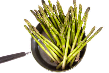Ripe Asparagus in a pan ready to be cooked on a white background photo