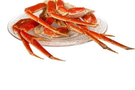 Crablegs cooked and placed on a fancy clear plate on a white background photo