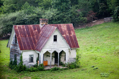Very old weathered country home with pasture photo