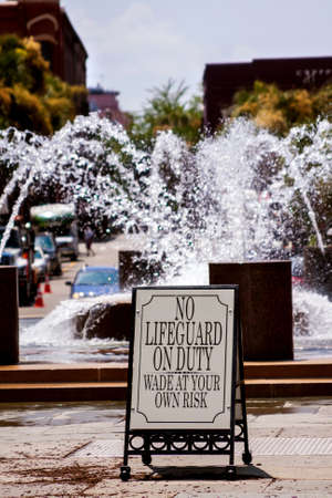 Fountain in the city with a warning sign photo