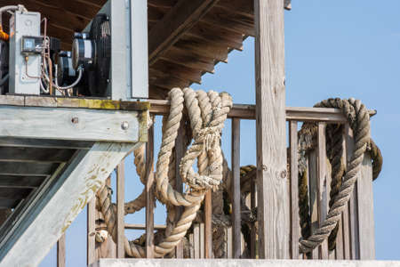 Large old ropes hanging on the deck railing Stock Photo