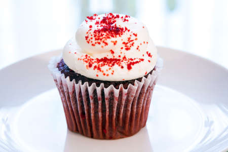 Red Velvet cupcake on a plate with white cream cheese frosting and sprinkled with red sugar Stock Photo