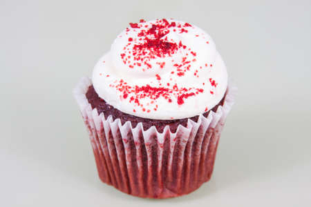 Red Velvet cupcake with white cream cheese frosting and sprinkled with red sugar