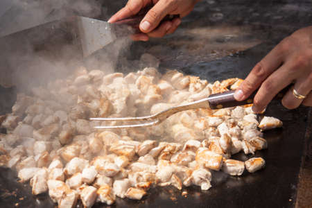 Cooking chopped chicken on the grill for stir fry