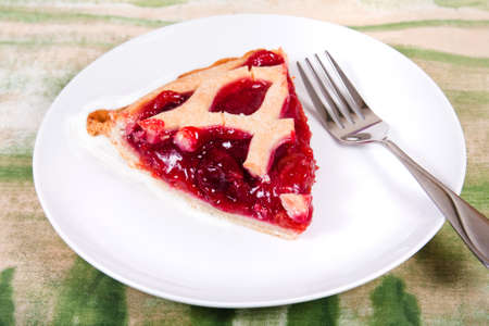 Piece of sweet cherry pie on  a plate with a fork