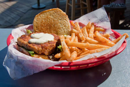 Crabcake sandwich with french fries in a basket Stock Photo