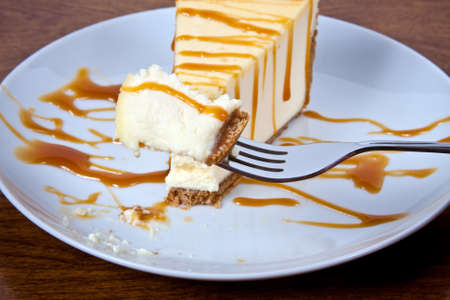 Cheesecake With Carmel Drizzled on Top Served on a White Plate