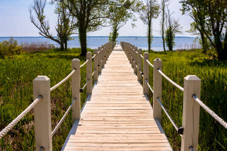 Wooden walkway leading out to the ocean Stock Photo