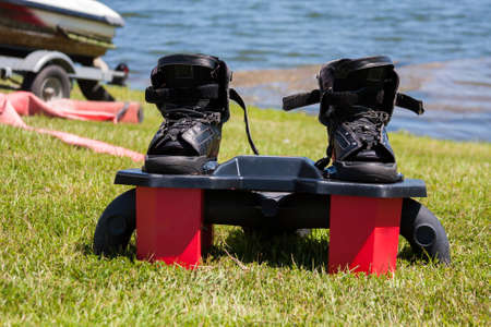 Fly boarding boots sitting on the grass at the lake