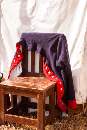 Civil War coat hanging on a chair in front of a tent Banque d'images