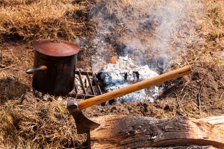 Cooking dinner over an campfire with axe