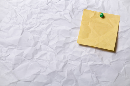 posted: Blank Yellow paper posted on crumpled paper sheet with tack pin for text and background Stock Photo