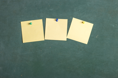 tack board: Blank Yellow paper posted on green board with tack pin for text and background