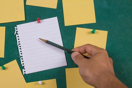 posted: Male hand with pen writing on notebookBlank Yellow paper, posted , ,note ,Sticky Note