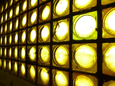 An old yellow glass bricks wall with back lighting by rounds Stock Photo - 12678773