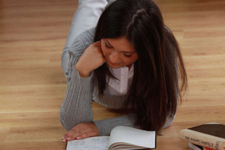 one room school house: Young beautieful, natural looking, caucasian, brunette girl learning on the flor with red pen and books Stock Photo