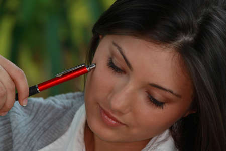 Young beautieful, natural looking, caucasian, brunette girl learning on the flor with red pen and books Stock Photo - 4679817