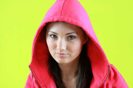 Portrait of young beautiful teen girl in pink hood on green background photo
