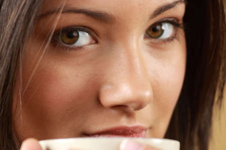 Young woman with beautiful face is having her tea/coffee photo